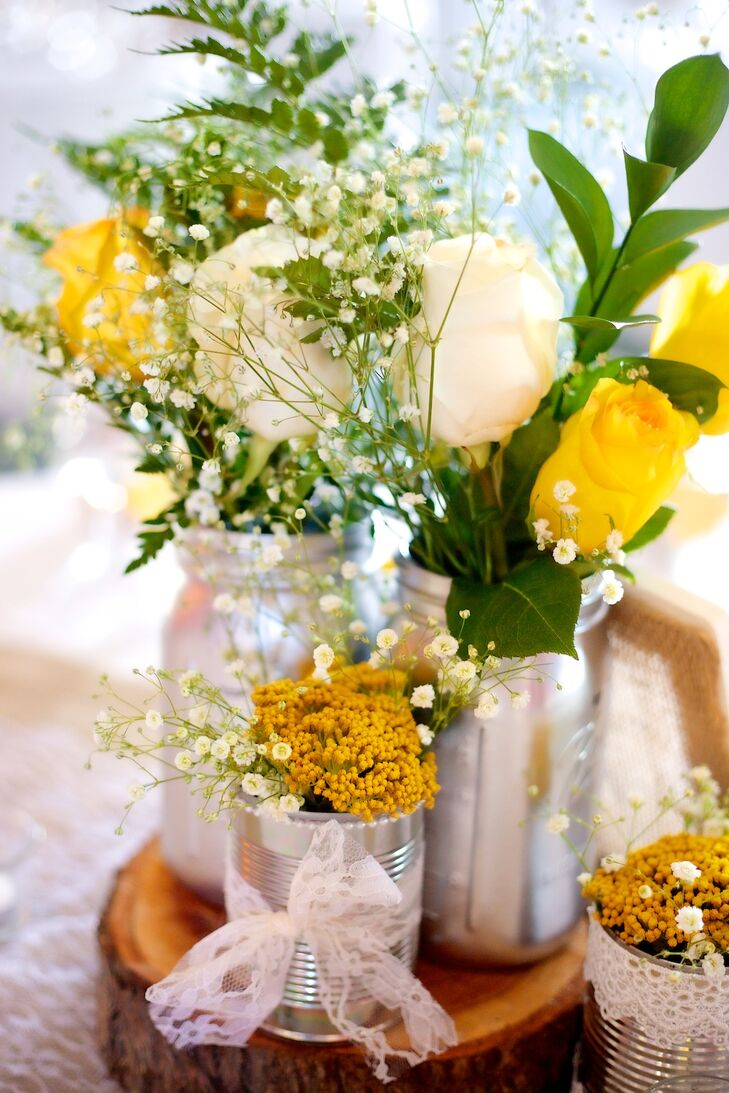 "The couple made the table centerpieces, which were painted mason jars filled with yellow and ivory flowers accented with leaves. ""Our color palette was hues of yellow, white and ivory, and the wedding style was rustic, chic and country,"" says Vanessa."