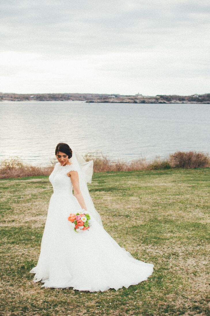For her bridal look, Yecelin was influenced by New England elegance. She chose a traditional lace ball gown with delicate lace cap sleeves, pairing it with a simple chapel-length veil for the ceremony. She wore her hair in a perfectly coiffed, low chignon and eye-catching crystal drop earrings.