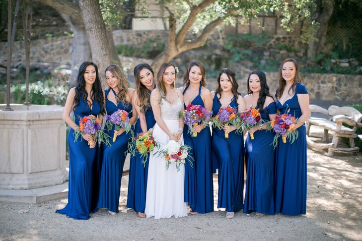 Lisa's bridesmaids donned deep peacock blue gowns and carried colorful bouquets made with crimson dahlias, zinnias and eucalyptus.