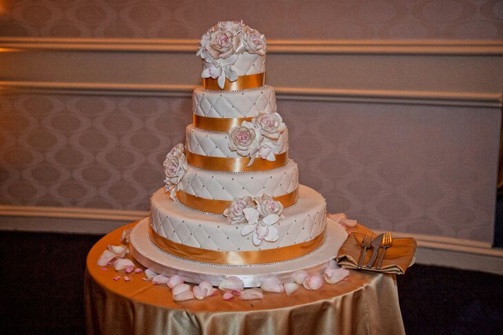The couple chose a five-tier white wedding cake with intricate details. Each tier had a gold ribbon tied around the bottom as well as roses and rose petals placed upon it.