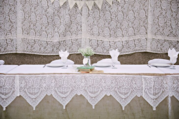 The head table was draped in burlap and lace for a rustic, vintage-inspired look.