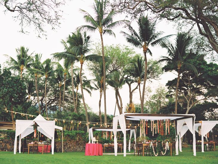 Guests sat at Kona wood farm tables under bistro lights and canopies draped with flower lei.