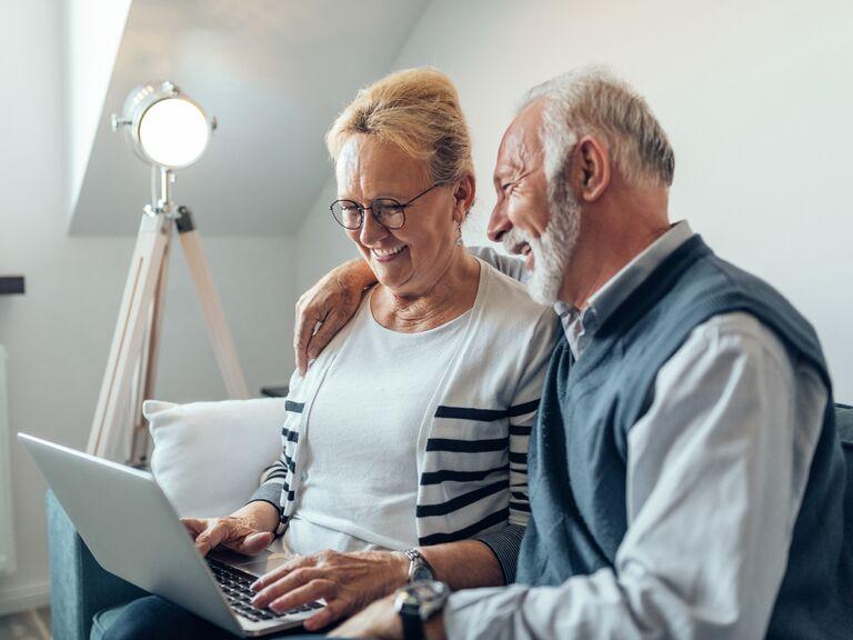 Older couple smiling watching something on their laptop