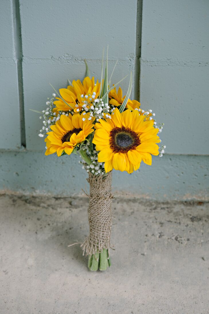 Emilie carried a bouquet with bright yellow sunflowers and baby's breath down the aisle. A burlap bouquet wrap gave the arrangement an added rustic note.