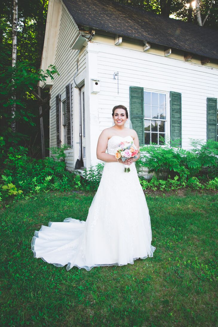 For her wedding day look, Laura went all-out classic. She donned an elegant A-line gown in a soft champagne hue with an ivory lace overlay and strapless sweetheart neckline. She styled her hair into a polished braided updo and added a fingertip-length veil for the ceremony.