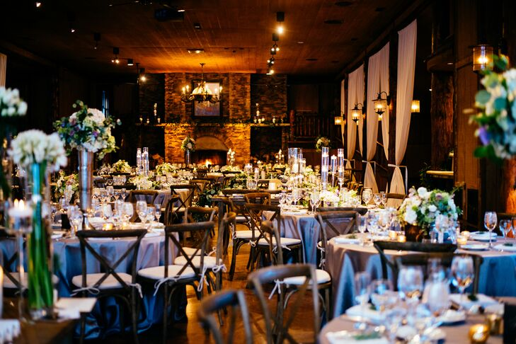 Wanting to play up their ultra-chic, rustic wedding theme, the couple added glamorous accents to the shabby chic ballroom. Meagan and James loved the natural rock fireplace, wooden ceilings and black iron lanterns of the space. They decorated with silver table linens to match the bridesmaid dresses and a mixture of tall and short centerpieces to add some dimension to the room.
