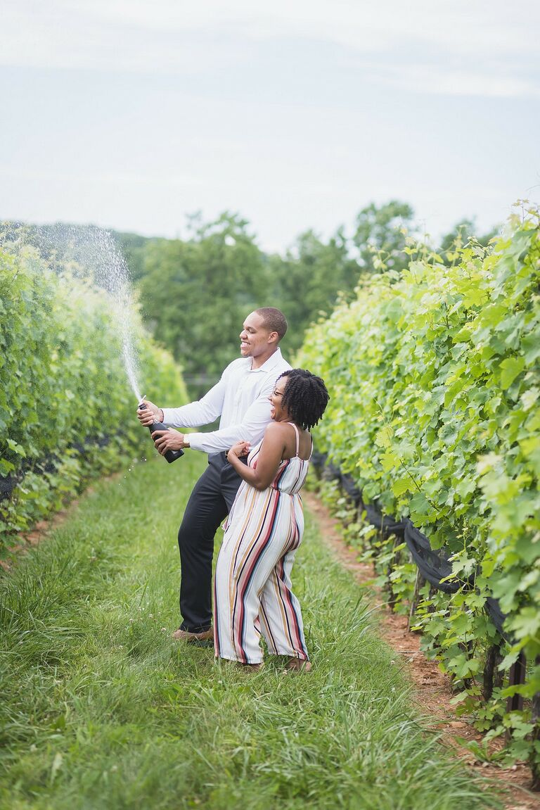 Couple sprays champagne during winery engagement session