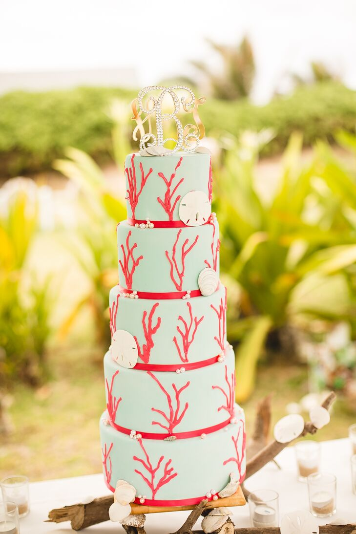 The teal wedding cake accented with coral reef designs had five tiers, decorated with seashells and beaded accents. Pineapple and coconut frosting covered the spice cake, making it look as tropical as the Oahu, Hawaii, wedding.