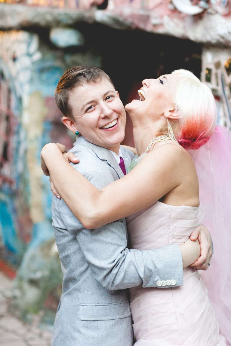 Bride wearing a blush wedding dress with matching hot pink ombre hair and a pink veil.