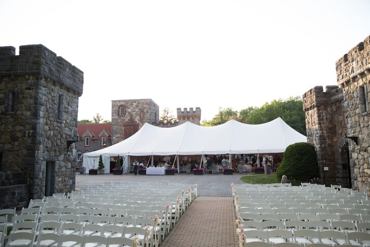The reception took place outdoors in the courtyard at Searles Castle in Windham, New Hampshire, where the couple and their guests enjoyed a night of dinner and dancing under an open-air tent. While guests mixed, mingled and nibbled on an inspired selection of bite-size eats, they were able to take in the venue's architecture, complete with impressive stone walls, turrets and lush gardens.