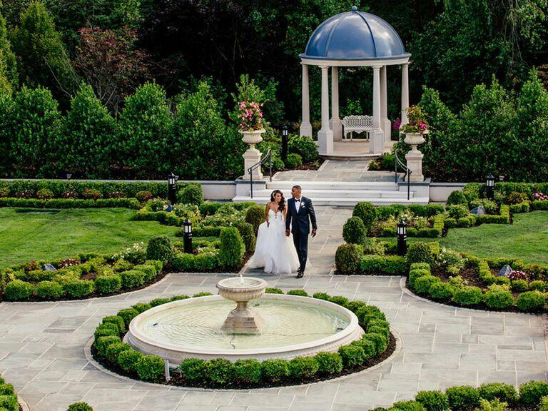 Bride and groom walking through secret garden wedding venue