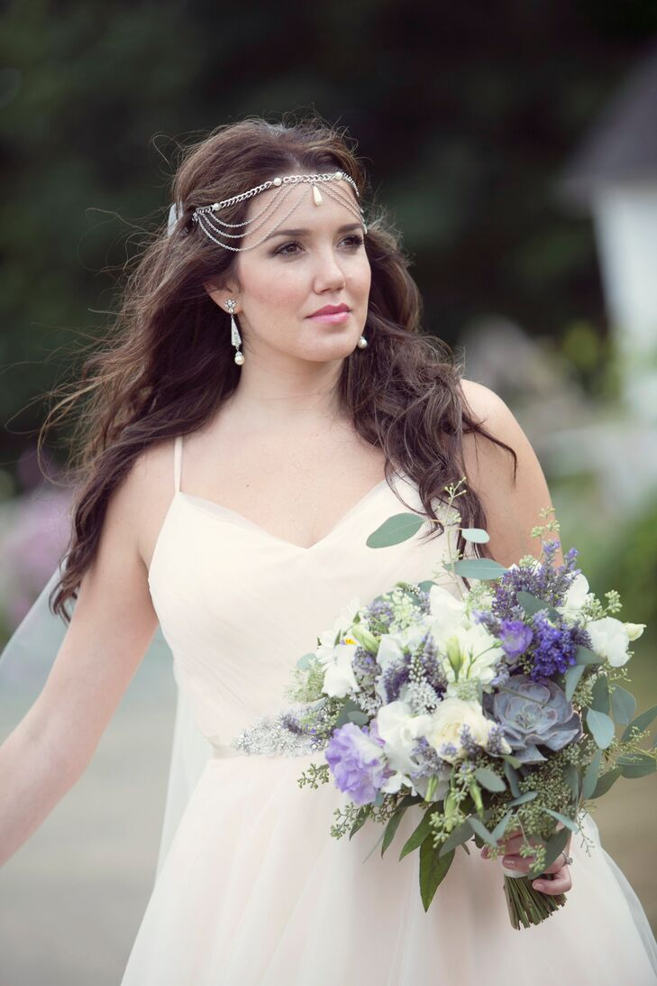 """Heather's cousin, Jenna, styled her wavy, down hairstyle. """"I literally could not have asked for a better look on my wedding day,"""" Heather says. She finished off the look with a gorgeous Bohemian head piece from Lovisa. For her bouquet, Heather incorporated rustic purple wildflowers with lots of earthy succulents to tie into the Bohemian theme."""