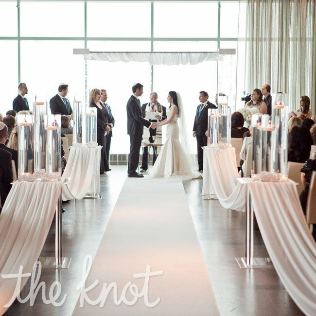 The modern ceremony space was decorated with tall cylinder vases and countless votives. The couple wed beneath a Lucite huppah.