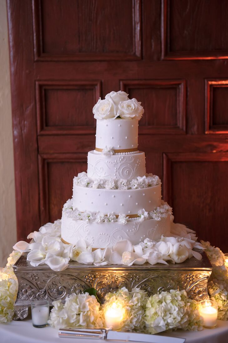 """Creative Cake Factory baked a classic all-white confection for Melissa and Derek that was composed of red velvet and chocolate cakes. A slight champagne ribbon along each base was met with white delphinium blooms and swirl or dotted piping. White roses served as the topper. """"I cannot wait to eat it on our one-year anniversary,"""" Melissa says."""