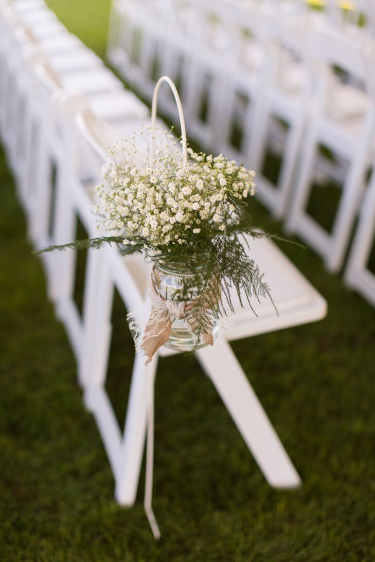 Clusters of baby's breath filled shepherd hooks with mason jars wrapped in burlap and lace, decorating the outdoor aisle.