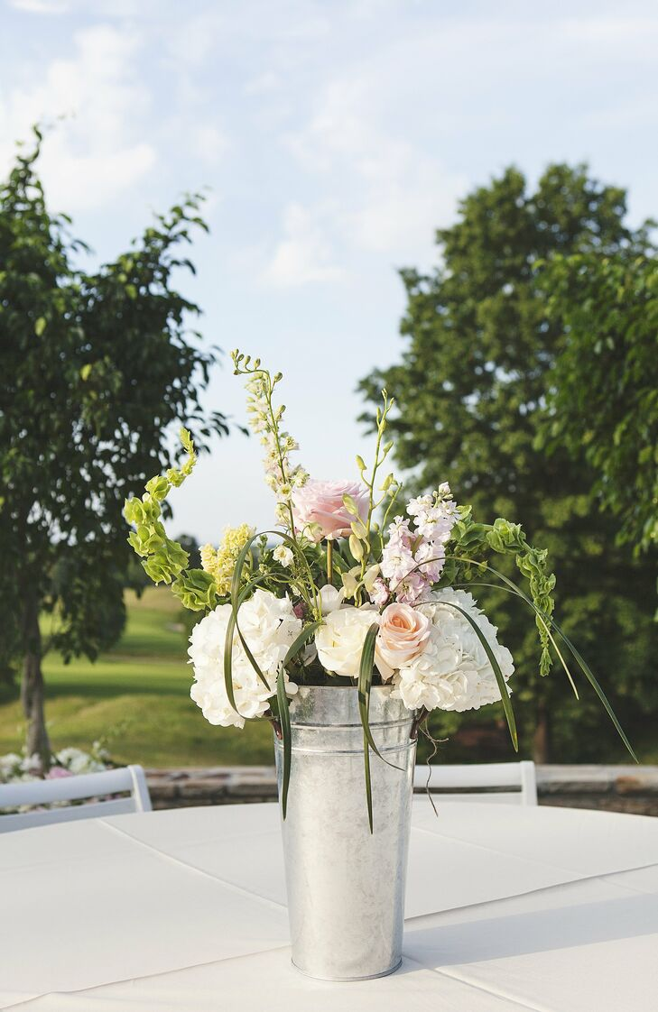 Galvanized pails filled with hydrangeas, roses, stock and belles of ireland added soft color to the outdoor celebration.