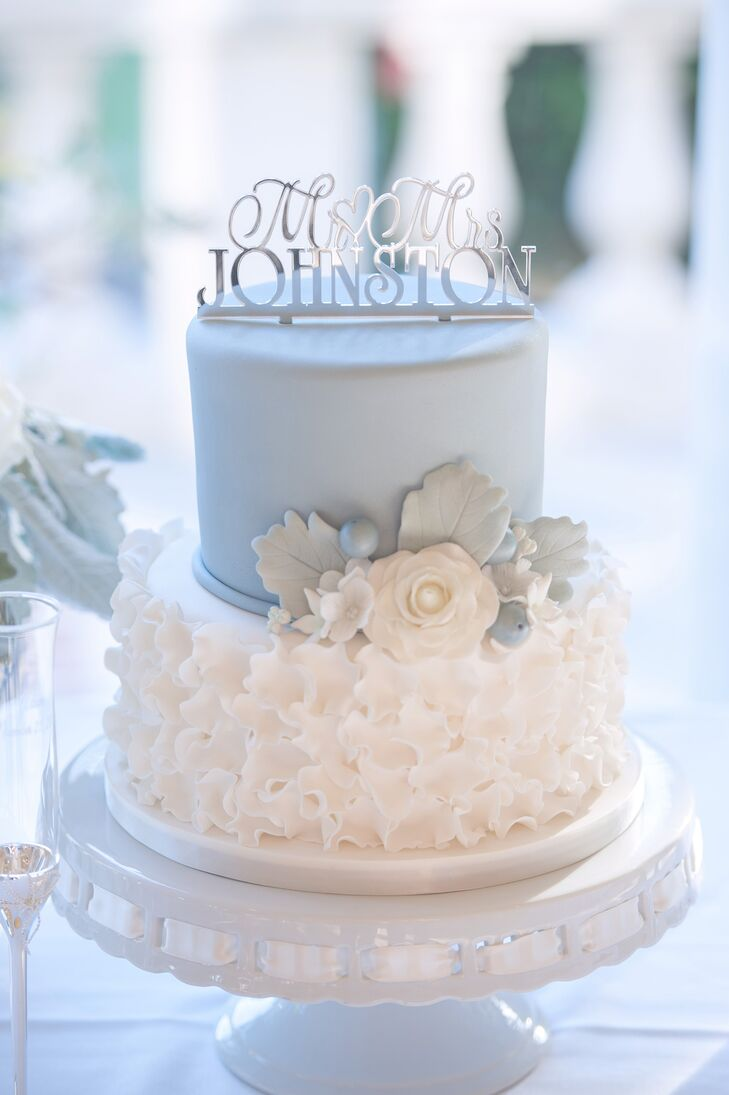 """While a sheet cake was used for serving, Abbey and Alex cut into a two-tier pale blue and ivory wedding cake. It was accented with a white cake flower and dusty miller. """"I found a picture of a cake online and the cake vendor matched it exactly,"""" says Abbey."""