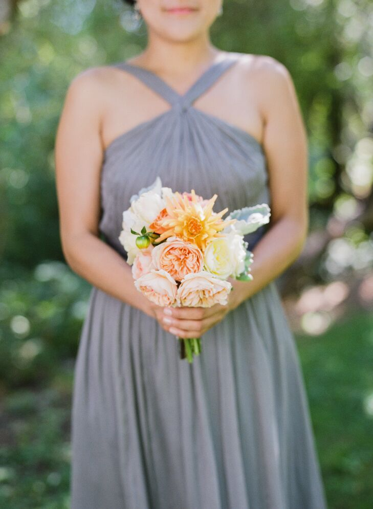 The bridesmaids held bouquets filled with garden roses, chrysanthemums, roses and several other blooms in shades of pink, orange and white. The soft flower arrangements went nicely with their romantic gray dresses.