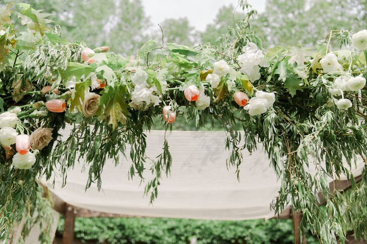 Sarah and Paul's custom chuppah included a special nod to their Jewish culture: the seven species of food--wheat, barley, grapes, figs, pomegranates, olives and date honey--were intertwined throughout the weeping greenery.