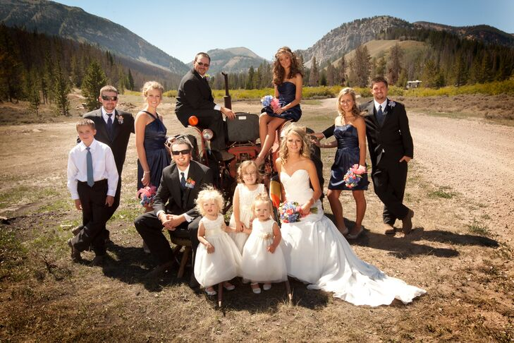 The bridesmaids wore strapless navy cocktail dresses and the groomsmen wore black suits with navy ties. They added a pop of color dark-colored attire with coral flowers in the bouquets.
