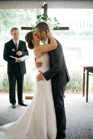 Bride and Groom's First Kiss in Front of Cross