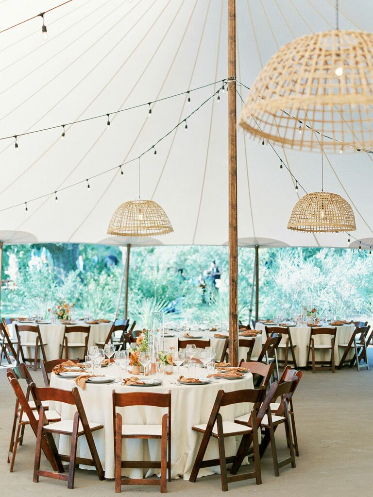 Neutral rattan chandeliers hanging from white outdoor wedding tent