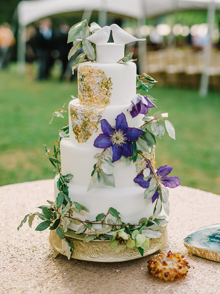 Romantic wedding cake with purple clematis and gold foil designs