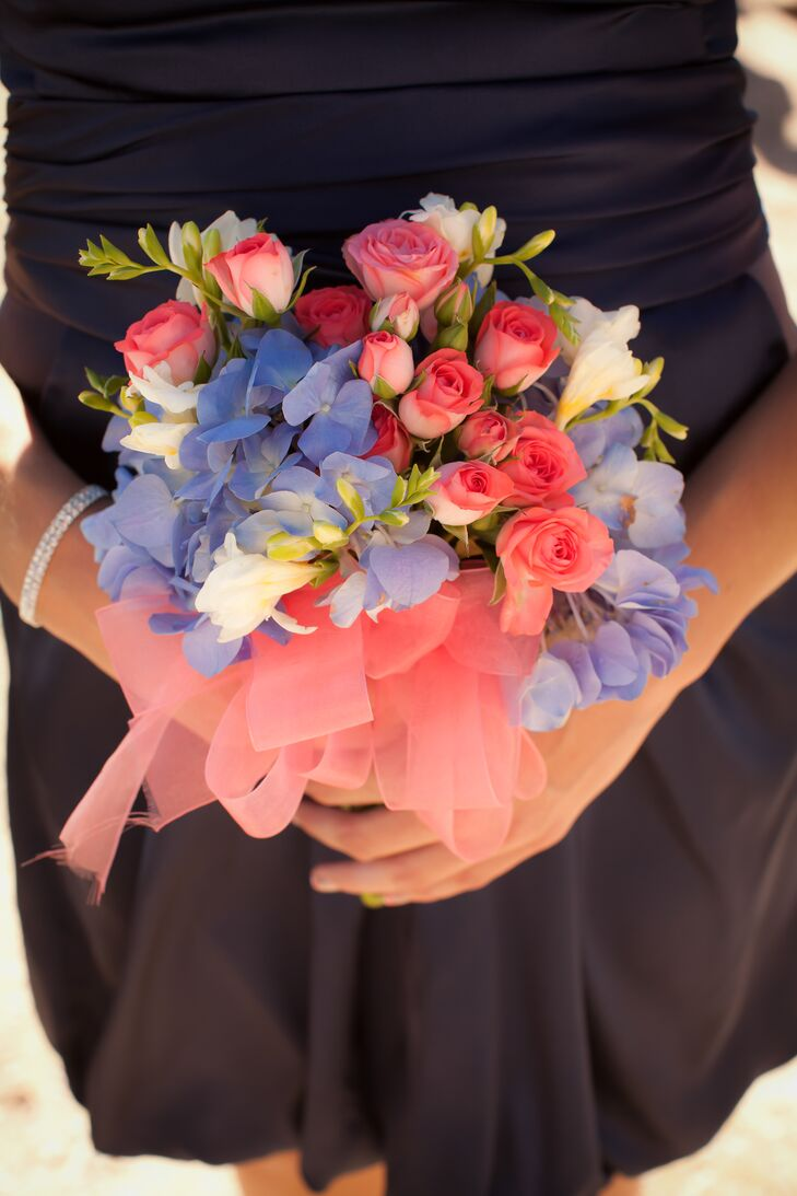 The bridesmaids carried pink roses with blue hydrangeas to match the coral and blue color palette. rn