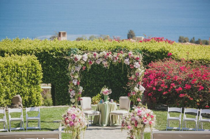 The couple exchanged vows overlooking the water beneath a gorgeous arch decorated with vines and flowers in shades of pink, green and ivory.