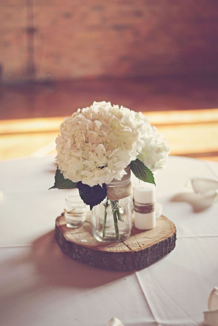 The bride's mother made their rustic centerpieces using spray painted old wine bottles wrapped twine. Family heirloom mason jars were filled with hydrangeas, baby's breath and and roses placed on wooden chargers.rn