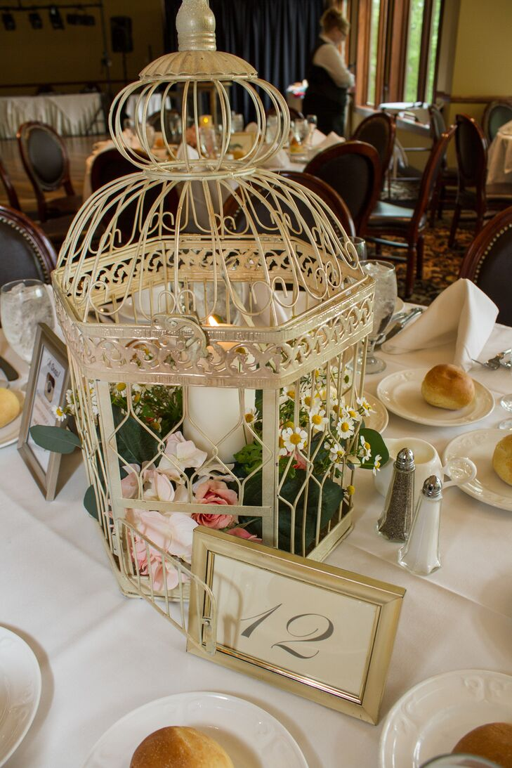 On alternating tables, wrought-iron birdcages housed a collection of seasonal flowers and greenery in pink and ivory and candles. Other centerpieces included tall manzanita trees accented with small blooms.