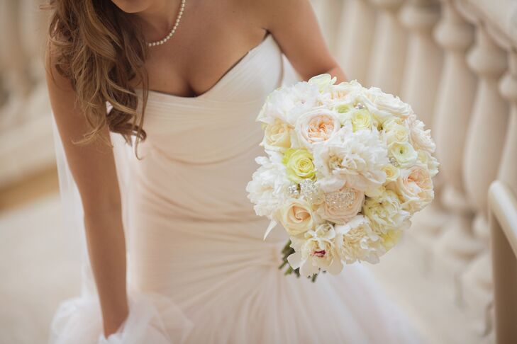 Megan carried a bouquet of pale yellow roses, white garden roses, white peonies, and white orchids arranged by Tiger Lily Flowers. Small crystal accents were placed within the bouquet.