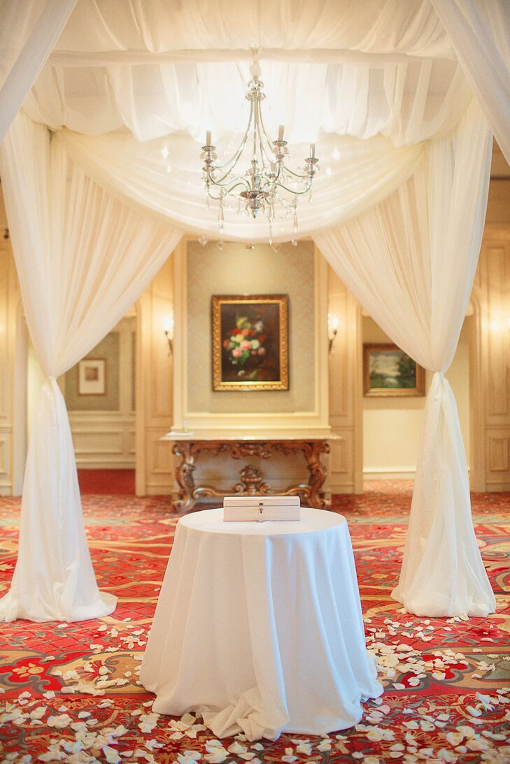 The couple's ceremony was decorated with white fabric draped throughout the room, white flower petals, low floral accents placed at the entrance and a simple table at the head of the room.