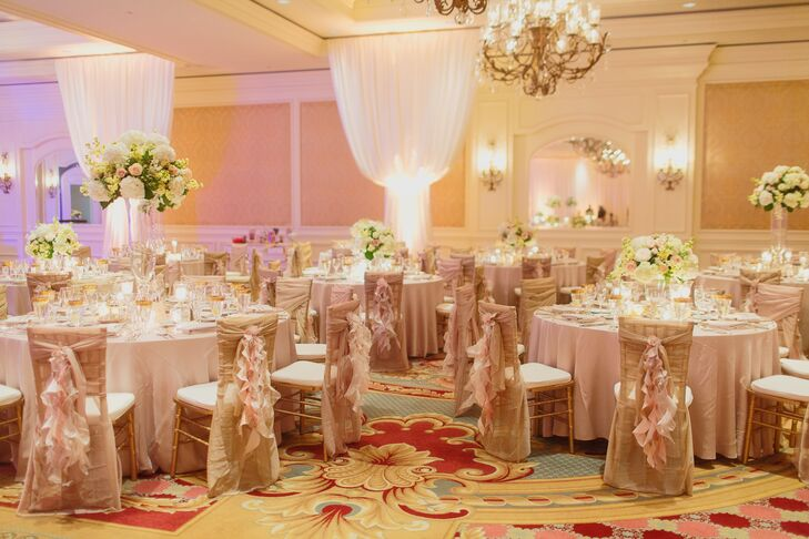 Gold chiavari chairs covered in champagne fabric and tied with blush ruffle sashes helped to decorated the couple's reception. Each table was covered with neutral linens, gold rimmed stemware and either a tall or low arrangement of white hydrangea and blush roses.