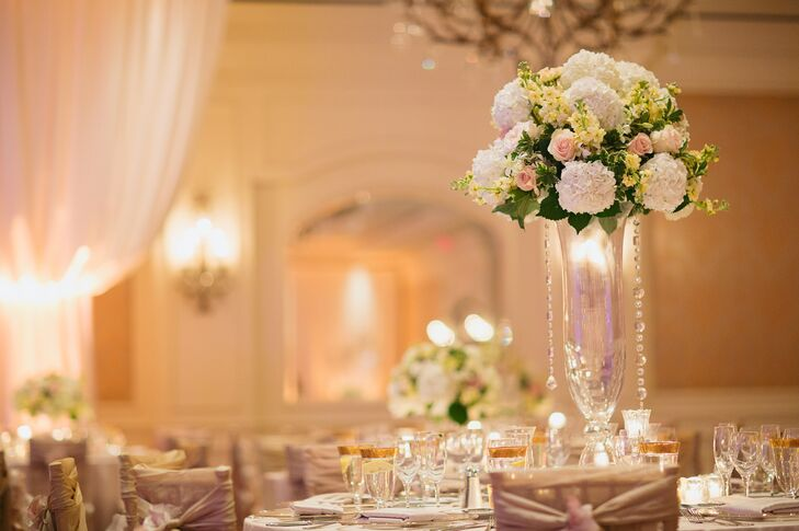 Megan and Josh's reception tables were accented with either a low or tall arrangement of white hydrangea, blush roses and yellow lilies of the valley.
