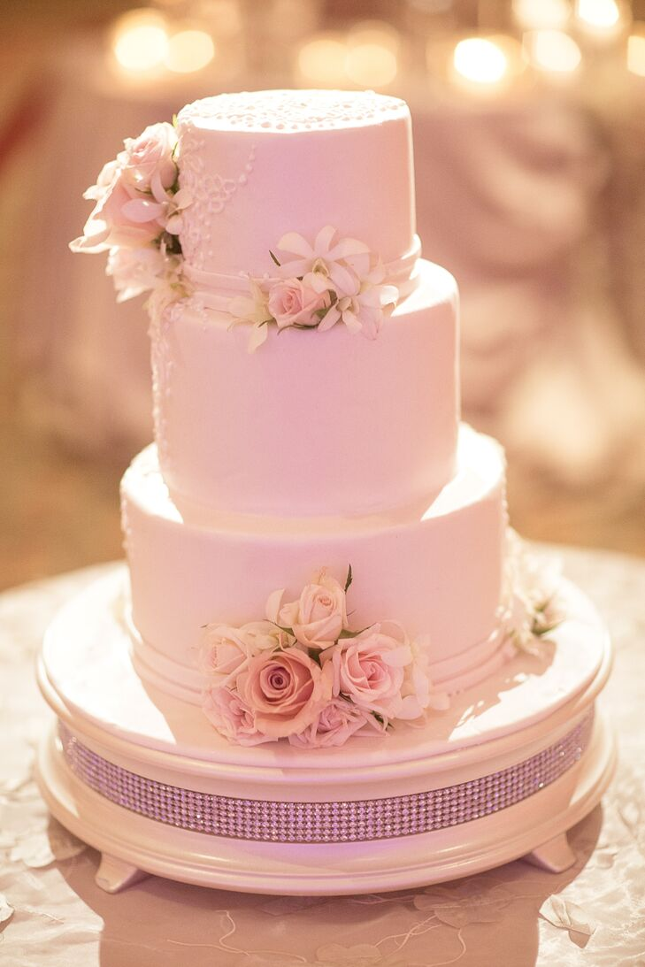 The couple chose a three-tiered white confection with a delicate piping detail and fresh blush roses as accents.