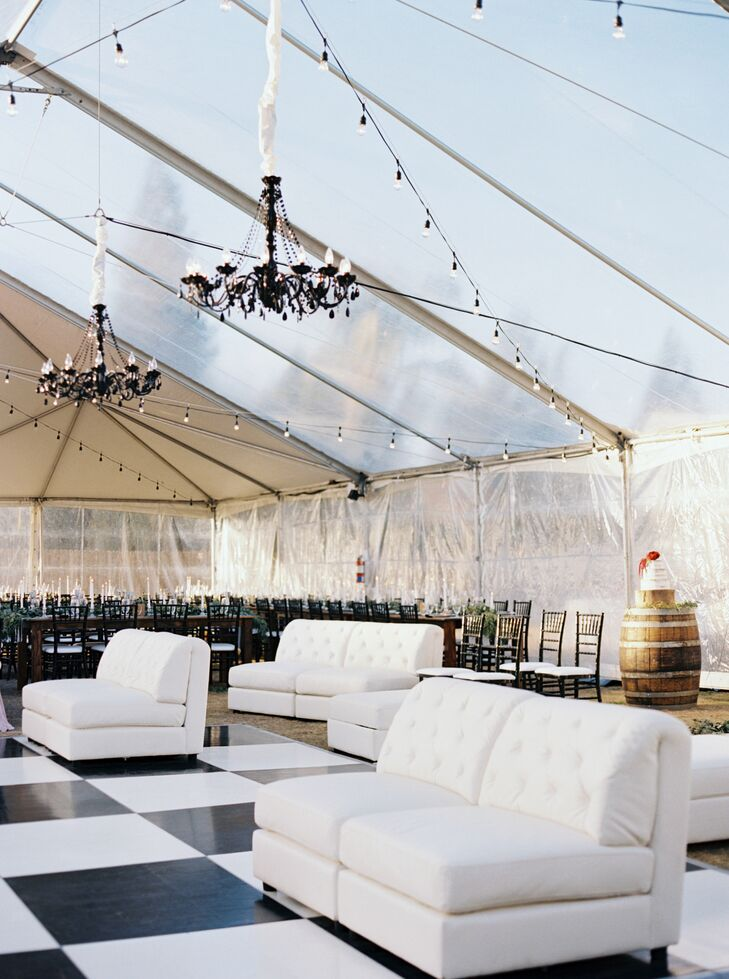 Inside the clear reception tent, chandeliers hung over a striking black-and-white-tiled dance floor, which was paired with chic white lounge furniture.
