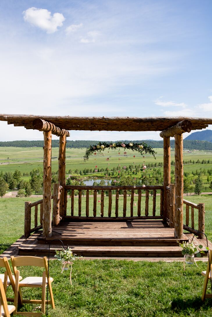 Meghan and Dane were married at the classic wooden pergola located outside at Spruce Mountain Ranch in Larkspur, Colorado, with a gorgeous backdrop of the landscaping. A garland accented with blooms hung from above like an elegant chandelier.