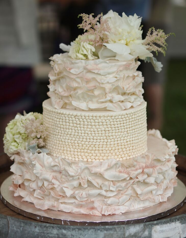 """Laura's best friend (and bridesmaid) baked the couple's three-tier wedding cake. At the request of the bride, blush and white ruffles accented the bottom and base tier for an eye-catching look. The center tier was decorated with lines upon lines of a dotted, piped design,  For an added touch, white hydrangeas, white peonies and pink lavender were used as accents. """"It turned out more beautiful than I imagined,"""" Laura says."""