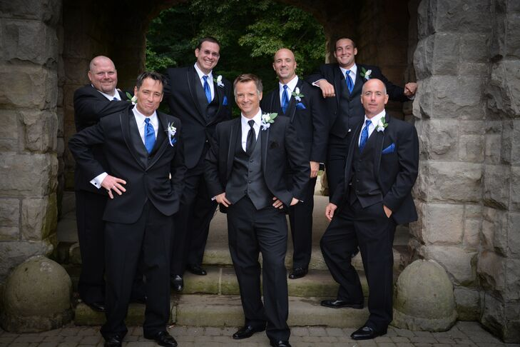 The groom stood with his groomsmen, all dressed in black tuxedos. The groomsmen wore bright blue ties while the groom wore a black tie.
