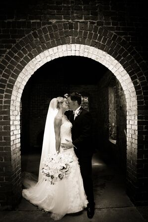 Married Couple Kissing Under Arch