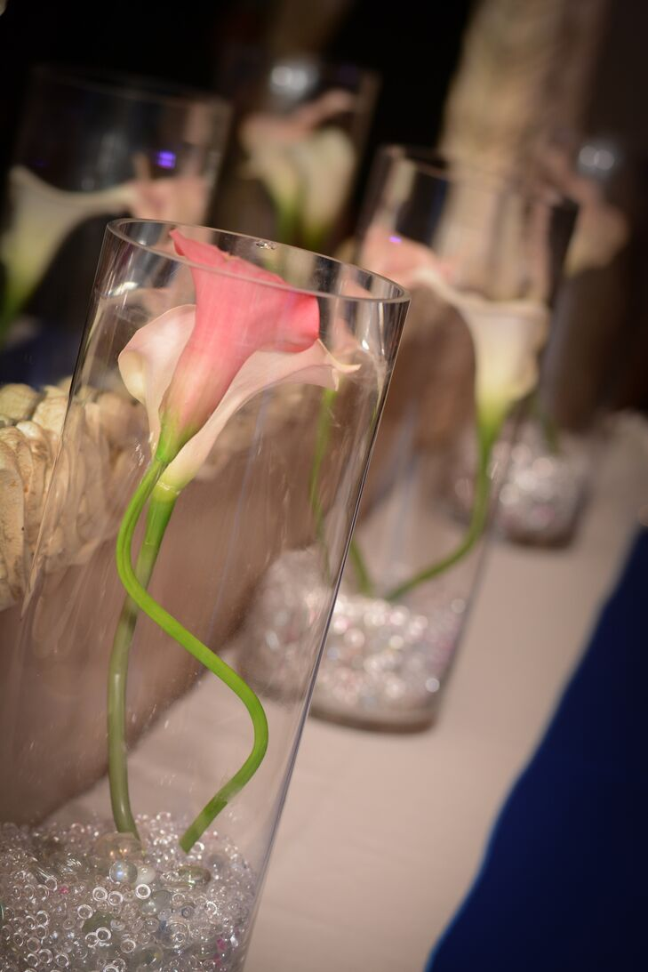 Pink calla lilies were arranged in white cylinder vases and decorated the reception at La Vera Party Center venue.
