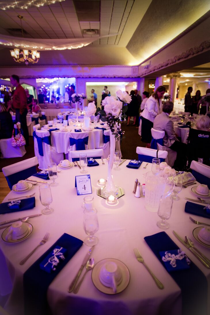 Dining tables were dressed in white tablecloths accented with blue napkins. In the center of the table were candles and a tall ivory flower centerpiece.