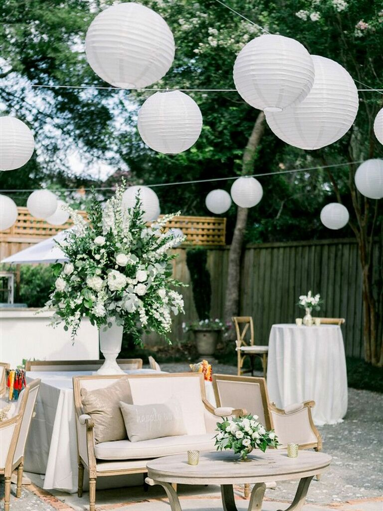 White paper lanterns strung as wedding reception decorations at outdoor venue