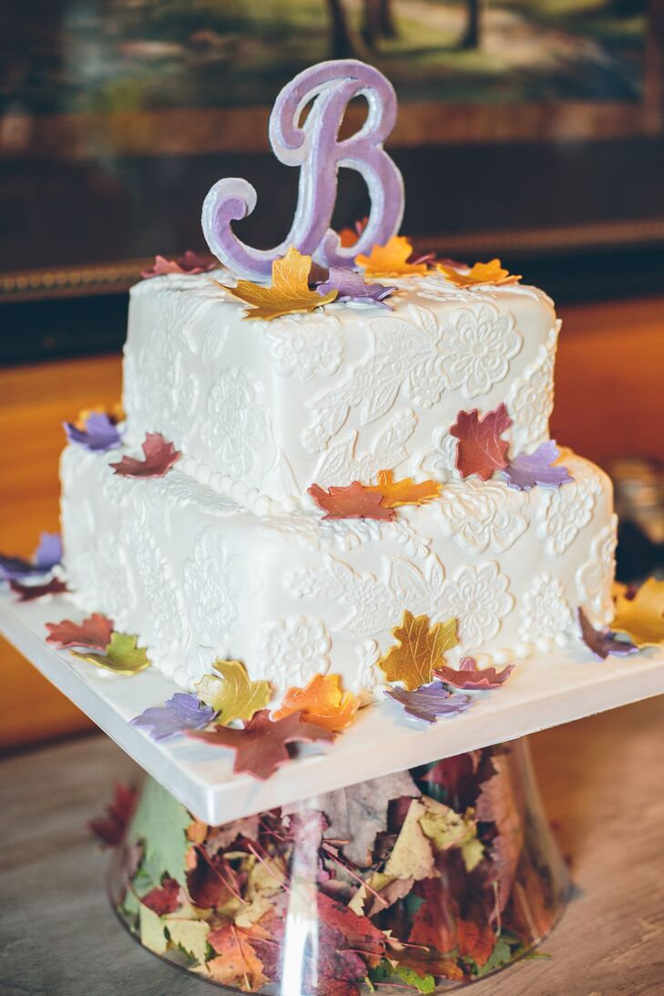 Melissa's Custom Cakes created a two-tiered square cake sprinkled with rustic fondant leafs.