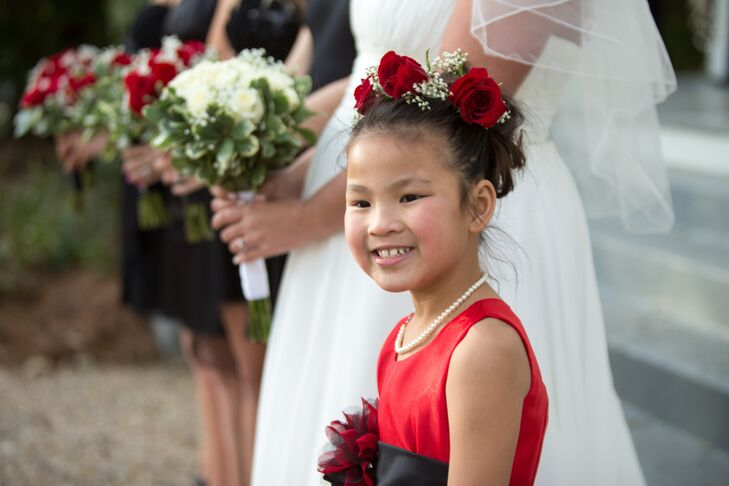 Instead of the more traditional white dress, the flower girl walked down the aisle in a bright red number and a matching red rose flower crown.