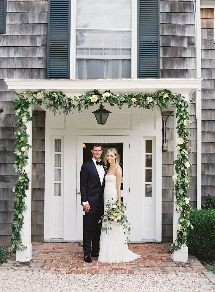 "The couple gathered their family at Ram's Head Inn in Shelter Island Heights, New York, for an intimate rustic soiree with endless elegant appeal. ""Shelter Island is a really meaningful place for us and our families. Ram's Head Inn is minutes from my family's summer home and has the most beautiful, quintessentially Shelter Island setting—on a hill just past the Ram Island causeway, overlooking Coecles Harbor,"" Jenna says. As guests arrived to the fete, they passed under a striking garland of greenery and full white blooms."