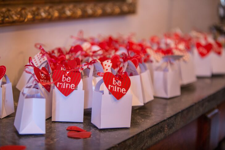"""Bright read hearts with traditional Valentine's messages like """"Be Mine"""" added a playful touch to the wedding favors and fit perfectly with the wedding's theme."""