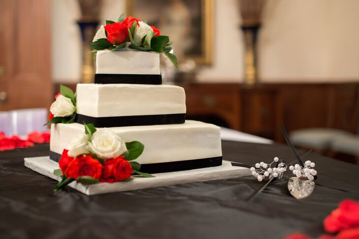 After a meal, which included everything from a mashed potato bar, to shish kabobs and Texas brisket, the couple served up traditional wedding cake. They kept the cake simple with three tiers of white fondant decorated with black fondant ribbon and clusters of red and white roses.