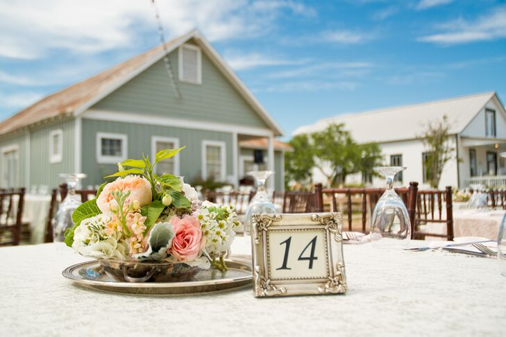 The reception was held outdoors on the main street. All tables were covered in sage satin with lace overlays, and the table numbers were framed in vintage, antique-looking picture frames.